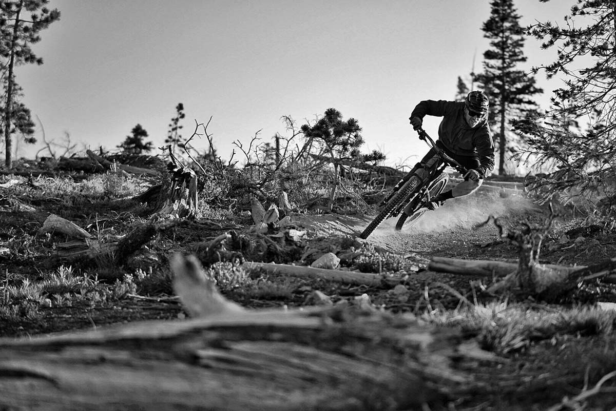 black and white photo of a mountain biker speeding around a corner on a dirt alpine track.