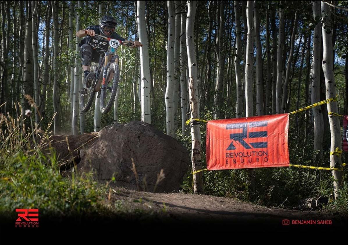 mountain biker leaps off a jump during a wooded race.