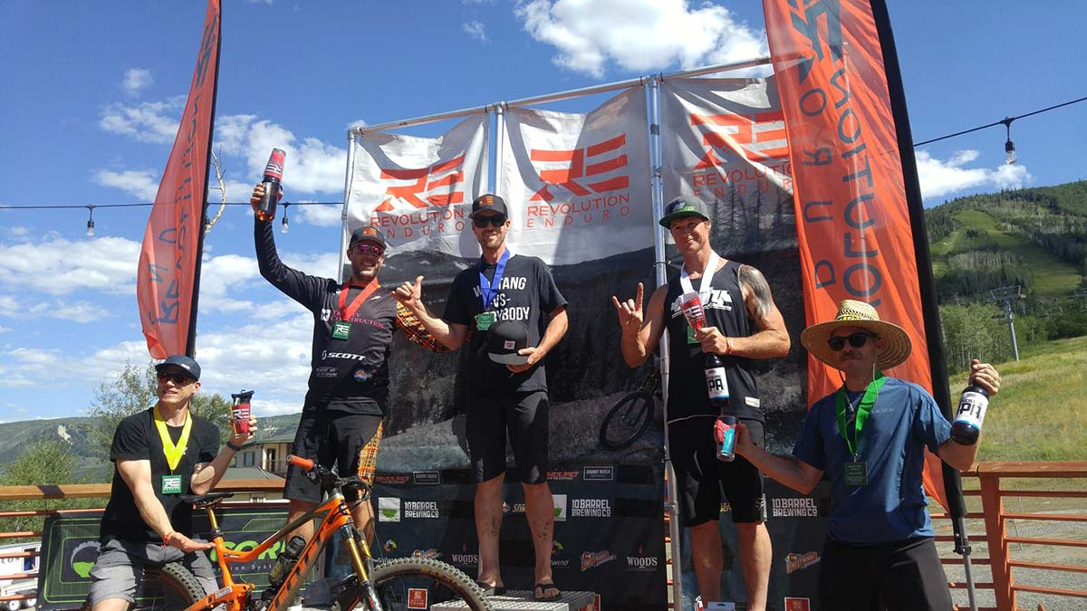 Three mountain bikers standing on an outdoor stage with their trophies.