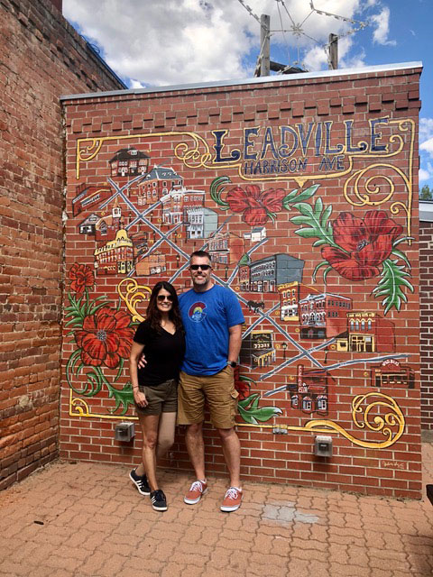 Angela with her husband in front of a mural on a brick wall.