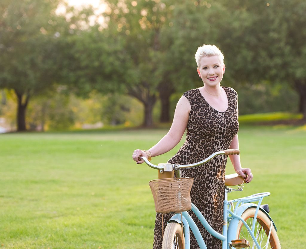 melanoma survivor Lauren Race poses with her blue cruiser bike at a Denver Park. She speaks out now about the dangers of tanning.