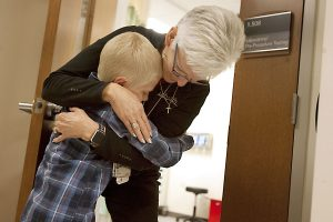 Boy hugs his phlebotomist at the hospital before a blood draw.
