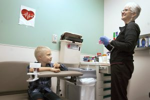 Boy sits next to his phlebotomist after she takes his blood at the hospital.