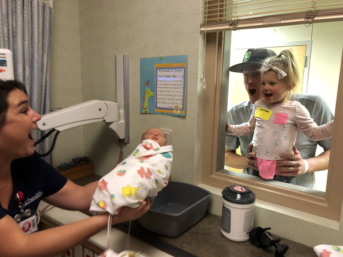 In this photo, big sister Eddy McDaniel looks at her new sister, Mimi, through a window.