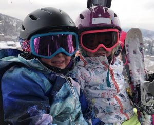 Two young girls are shown in ski gear, including helmets and goggles, in this photo.