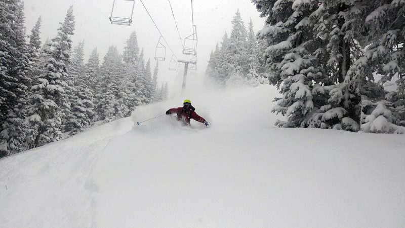 In this photo, a skier skis under a lift in chest-deep snow.