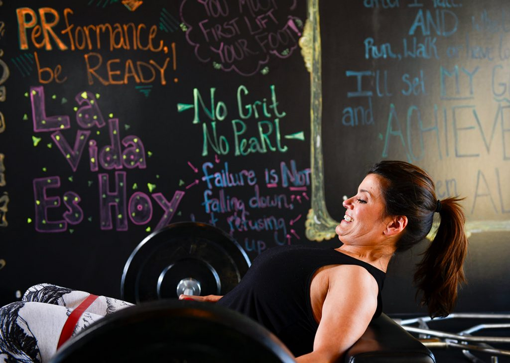 Fighting lymphedema after cancer. Angela lifts a barbell at her gym. Inspirational sayings appear on a wall behind her.