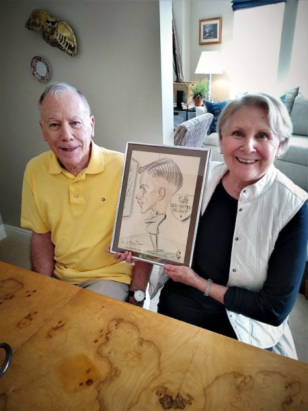 Wife holds a sketch of her husband when he was 21 while he, who is living with dementia and now 80, sits beside her.