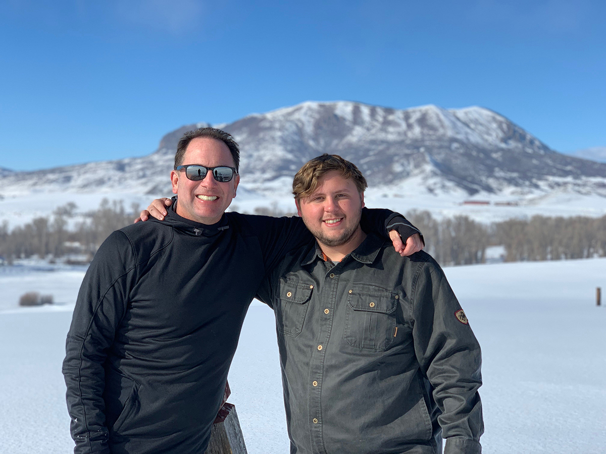 Dr. Richard Gitter and his son, Ben, stand in a snowy field in this photo.