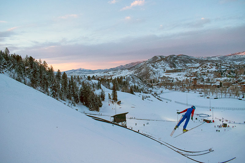 A skier flies off a Nordic ski jump in this photo.