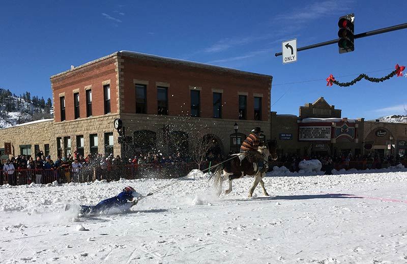 This is a photo of a shovel race, in which a participant rides on a shovel pulled by a horse on a snow-covered street.