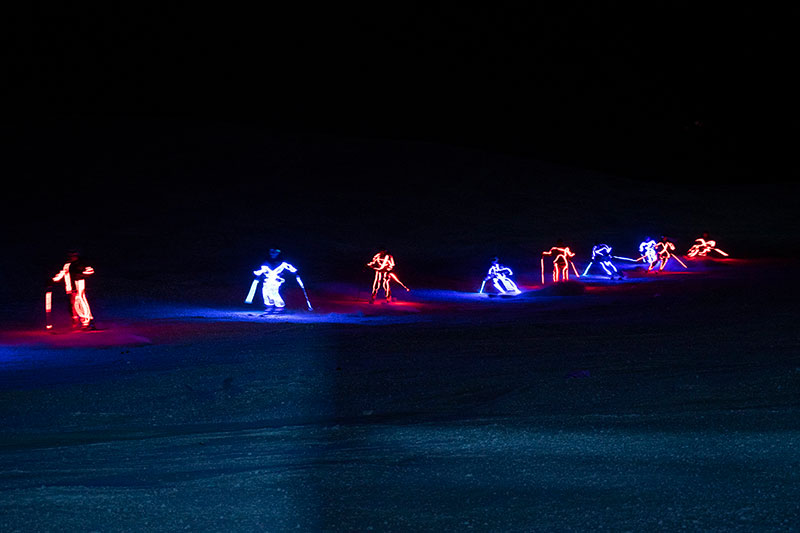 Skiers adorned with LED lights ski at night in this photo.