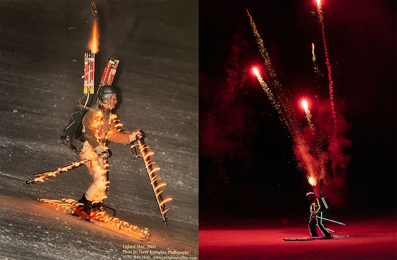 A man skis at night with lights and fireworks strapped to him in this photo.