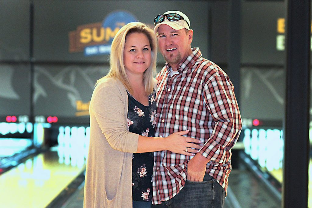dawn holds her husband for a photo in front of the bowling lanes.