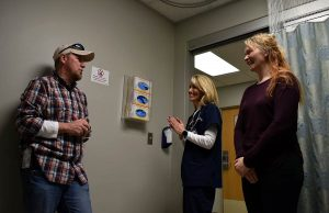 Keith talks with his urgent care doctor and nurse to thank them months after her was diagnosed with colon cancer that that urgent care.