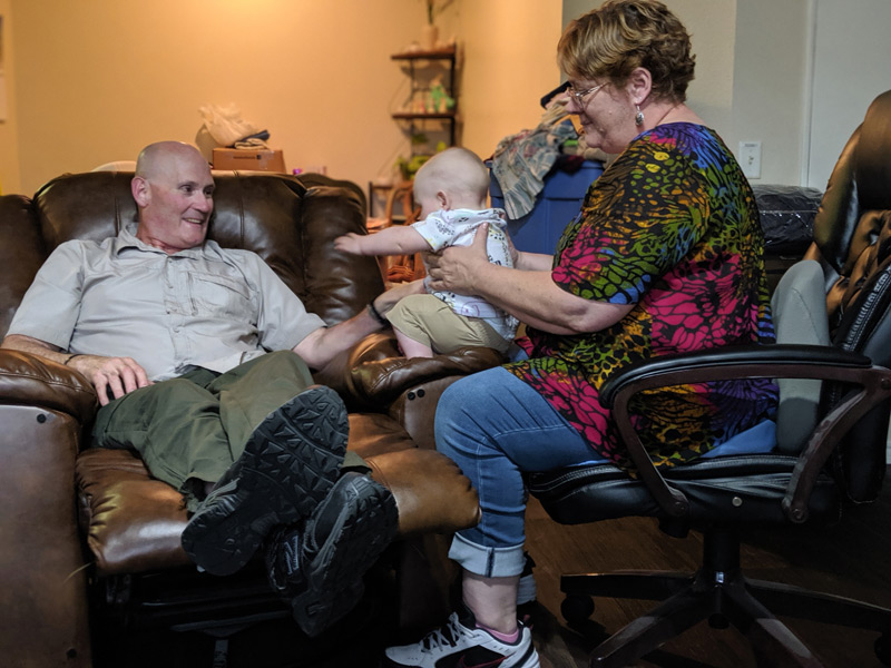 couple plays with their grandbaby in living room, something the grandfather might not be able to enjoy it it wasn't for CarioMems device that monitors his heart.