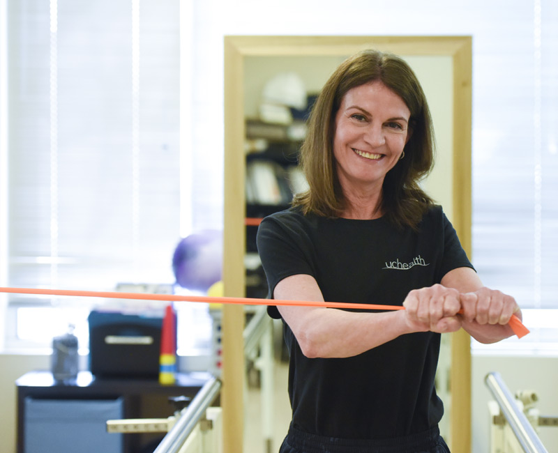 Woman looks at camera as she uses an exercise band with her arms.