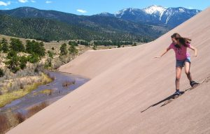 "A girl ""sandboards"" at Great Sand Dunes National Park and Preserve"