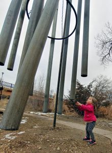 girl reaches up to play with massive chimes at the Swetsville Zoo, a free thing to do in northern Colorado.