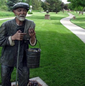 sculpture of old man carrying bucket of potatoes at a park.