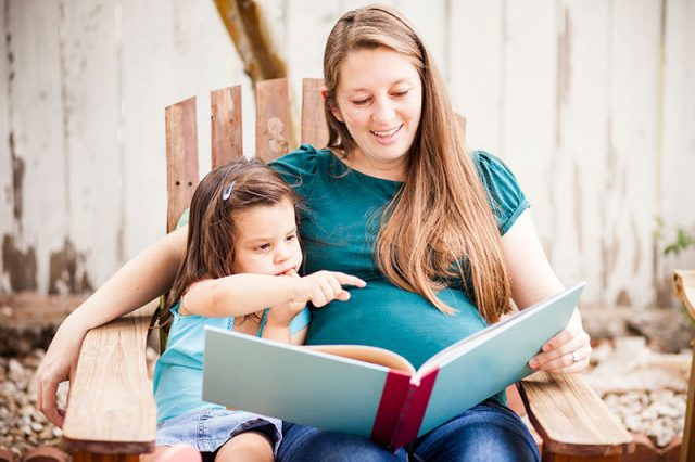 Pregnant mom sits with her young daughter reading a book. CDC says pregnant woman are more susceptible to the coronavirus, there is no evidence that children are.