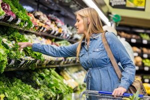 pregnant woman picks produce. the CDC cautions pregnant women about their increase vulnerability to the coronavirus.