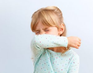 young girl coughing into her arm, one of the ways you can help stop spread of COVID-19 symptoms.