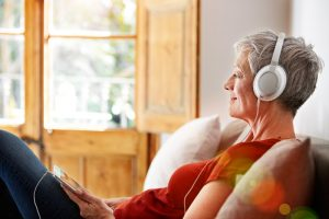 woman sits on couch with headphone. Listening to music is one of the ideas for social distancing.