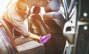 man disinfecting coronavirus in his car