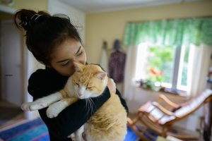 Woman hugs her cat, which as long as you are not sick with COVID-19 is ok for pet owners to do.