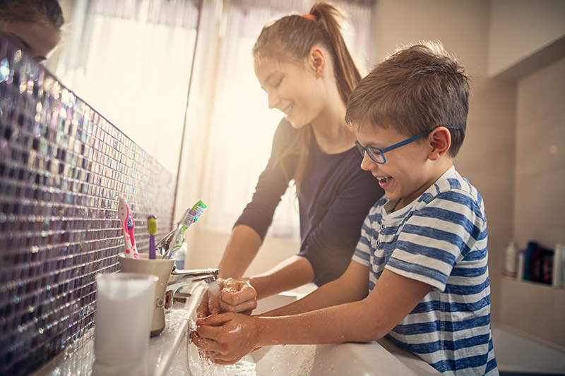 kids laughing while washing their hands. In coronavirus A to Z, S stands for sanitizer when hand washing isn't available.