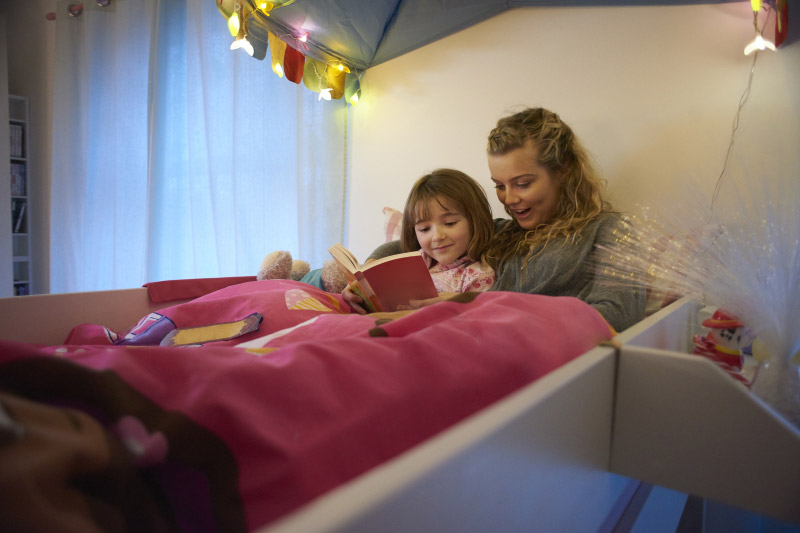 woman reading to a child in bed, one way in talking to children about coronavirus.
