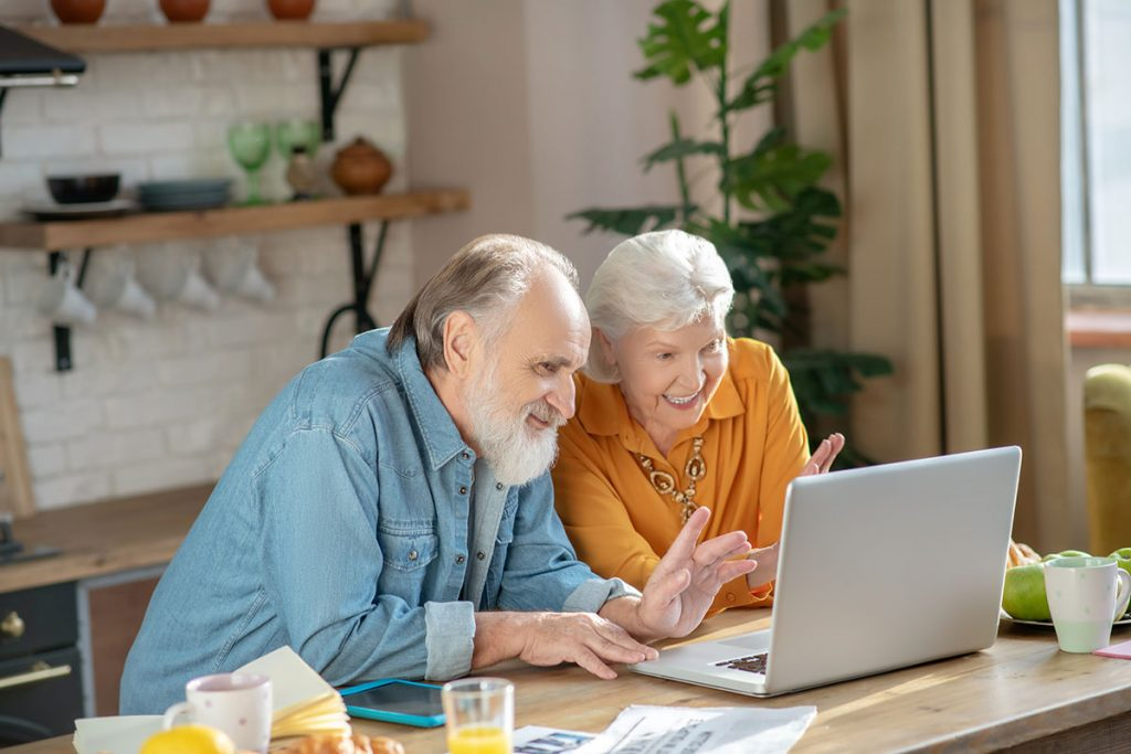 an older couple does a video chat on a computer