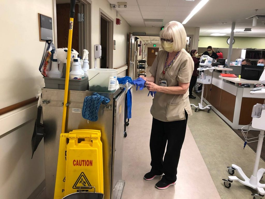 hospital housekeepers, like this one wearing a mask and gloves, are on the front lines during covid pandemic.