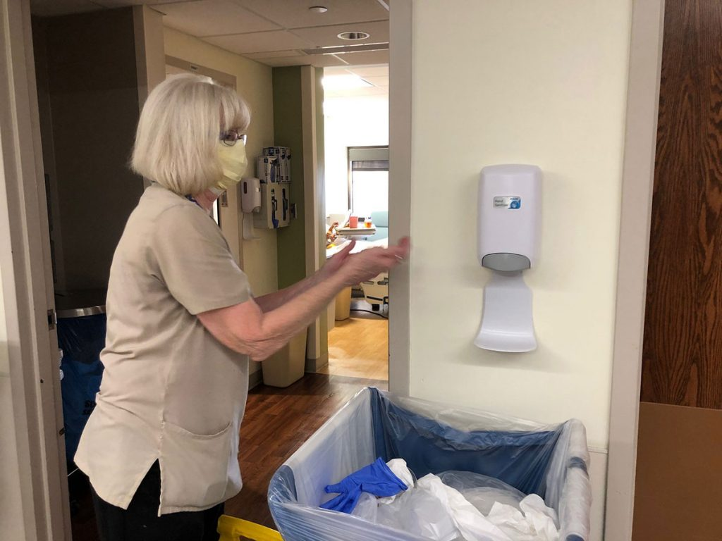 hospital housekeepers, like this one wearing a mask and reaching for hand sanitizer, are on the front lines during covid pandemic.