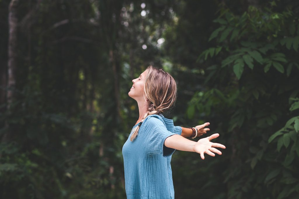 A woman opens her arms wide and breathes in fresh air as a way to practice emotional self-care