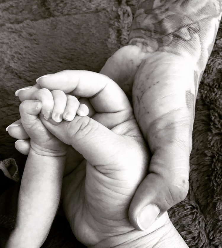hands of mom, dad and baby in black and white.