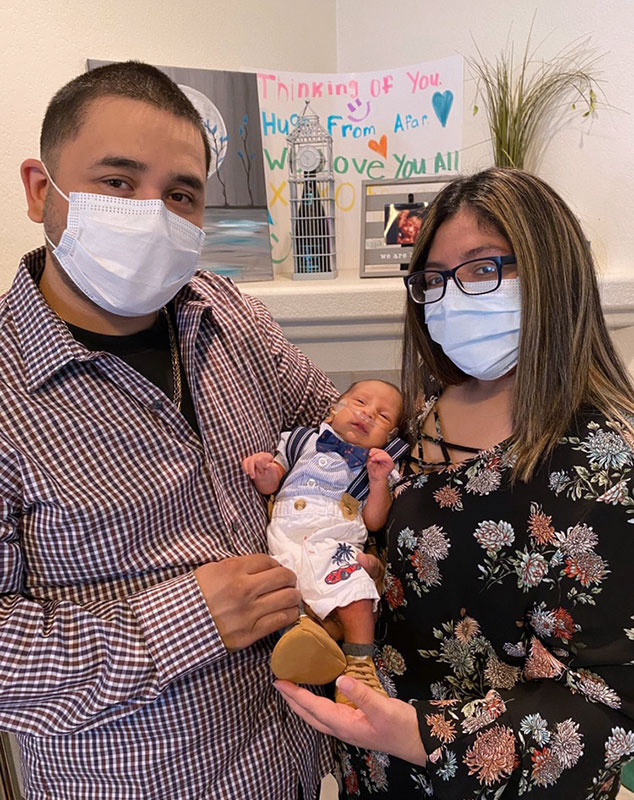 jade and Mikey, wearing masks and holding their newborn son.