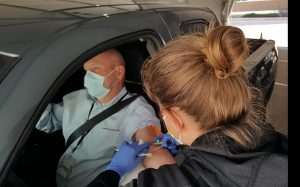 A nurse draws blood from a man who is seated in his car as part of a new drive-thru lab service in Colorado at UCHealth.