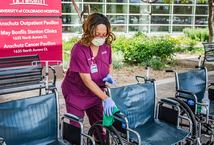 Hospital safety during COVID includes continuously cleaning regularly used areas and equipment, like this women cleaning wheelchairs outside the hospital