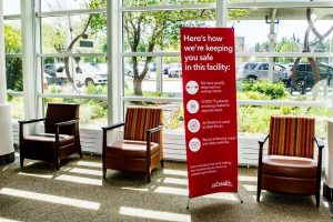 signs in a lobby explaining hospital safety during covid.