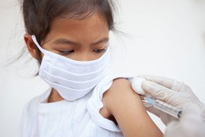 Child wearing a mask gets an child immunization during pandemic.