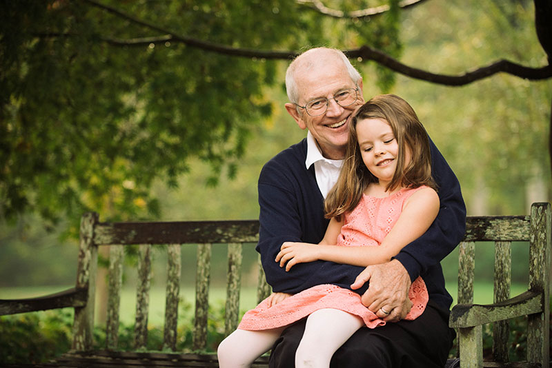 man, who is part of trial with blood pressure drug to fight pancreatic cancer, holding his granddaughter on a park bench.