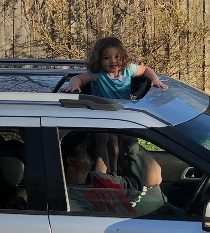 small child smiling while standing out of a car's sunroof.
