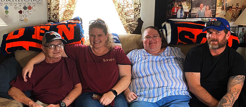 four family members sit on the couch for a photo, which was their christmas card in 2019 after one of them went from a LVAD to a heart transplant.