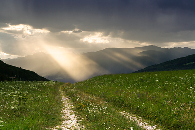 A stormy scene in the mountains with a ray of light signifying the impact of COVID-19 and suicides in Colorado.