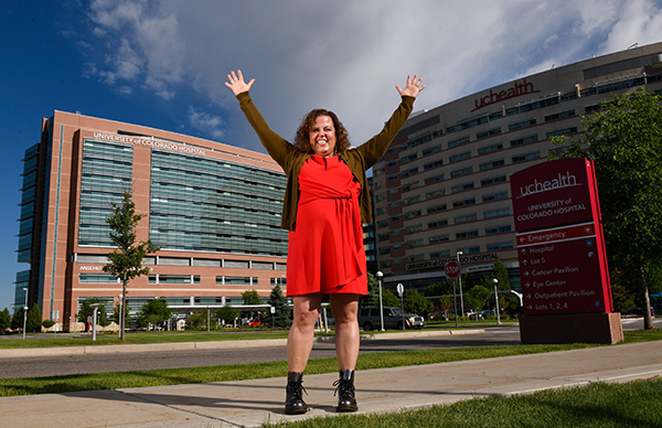 Dr. Michelle Barron is the top infectious disease expert in Colorado. Here she raises her arms as she stands in front of UCHealth University of Colorado Hospital.
