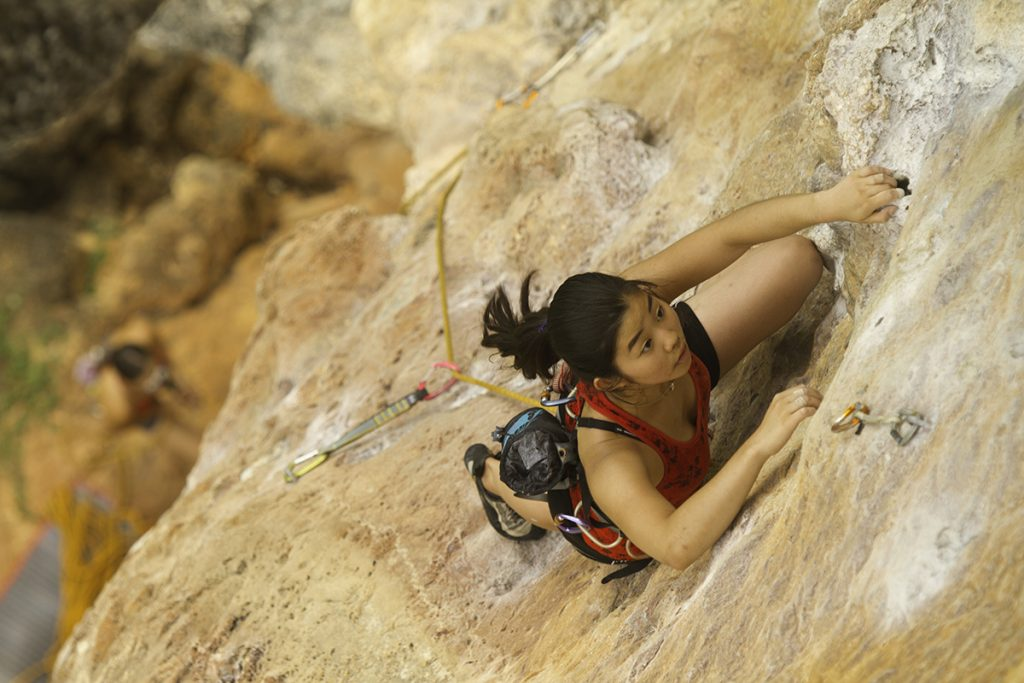 A woman rock climbs in this photo. Adventure safety is key, not matter how big or small the adventure.