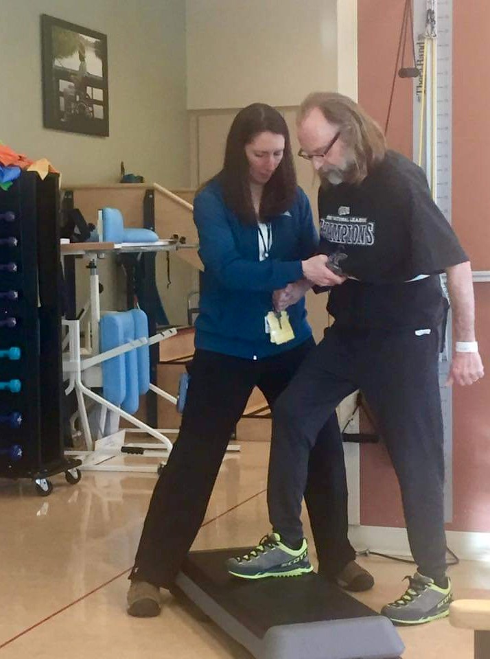 therapist at UCHealth hospital helping Jeff step up as part of his hemorrhagic stroke treatment.