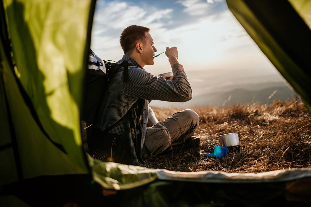 A man enjoys healthy camping meals outside his tent.